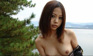 Asiatic girl with sunglasses on looks so seriously cause she is shy being naked